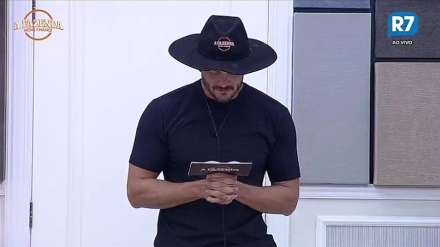 Marcos lê envelope enviado pela produção para atividade especial  - Reprodução/R7