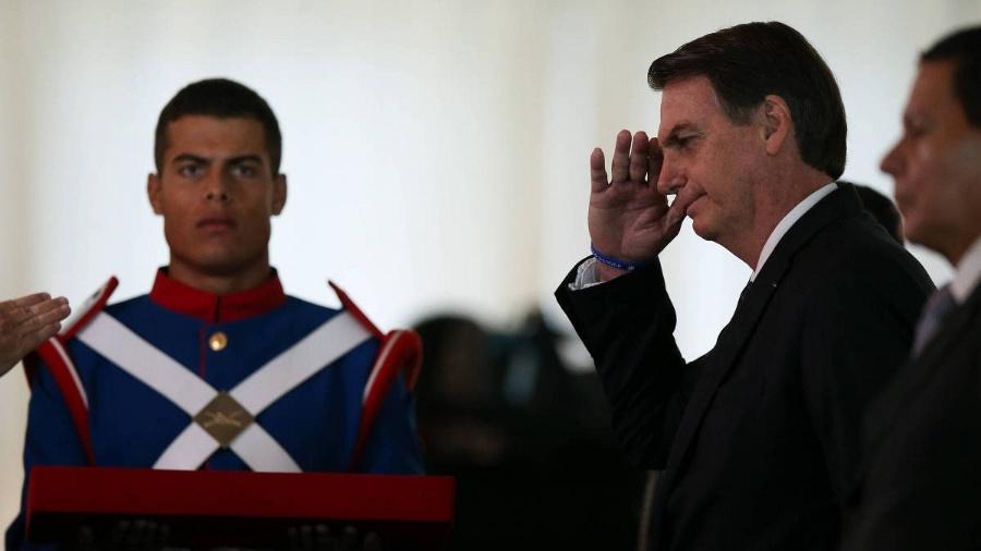 Bolsonaro presta continência ao lado do vice, general Mourão, em evento da Justiça Militar - Pedro Ladeira - 28.mar.2019/Folhapress