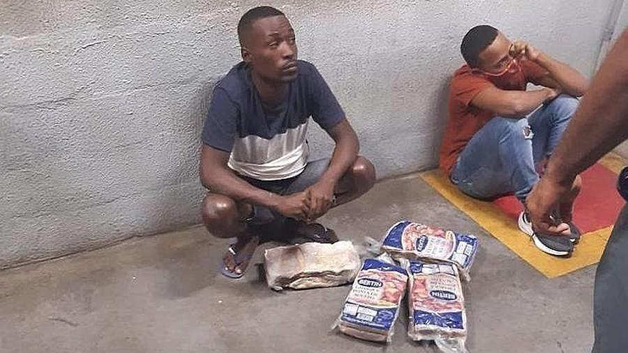Bruno e Ian sentados no pátio do supermercado ao lado dos quatro pacotes de carne furtados. Cada pacote custa em torno de R$ 188 - Reprodução/Redes Sociais