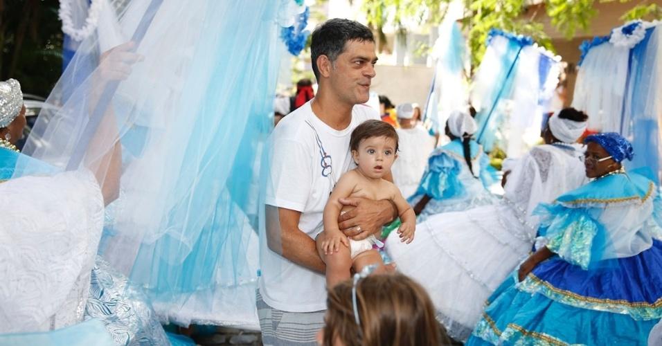 3.fev.2013 - O ator Du Moscovis, marido de Cynthia Howlett, acompanha o bloco com o filho Rodrigo no colo