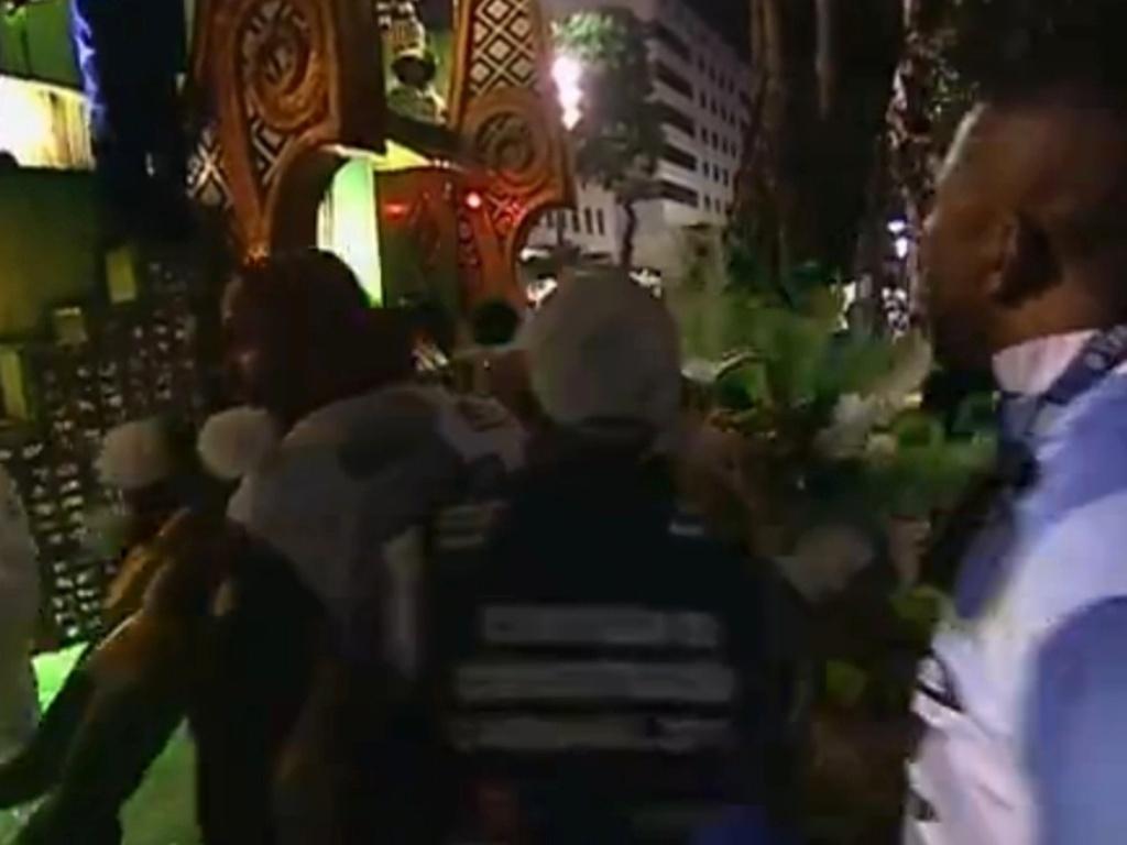 11.fev.2013 - Destaque da Portela, Anne Raquel, de 41 anos, quebra a perna após o carro da escola bater em uma árvore na concentração da Sapucaí. Na foto, o momento em que ela é carregada por integrantes da escola para um posto médico