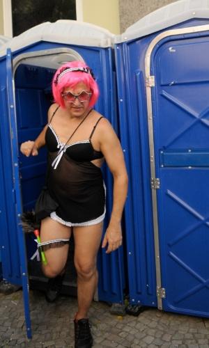 12.fev.2013 - Homem fantasiado de mulher sai de banheiro químico durante o desfile do Bloco das Quengas durante a terça de Carnaval no Rio de Janeiro