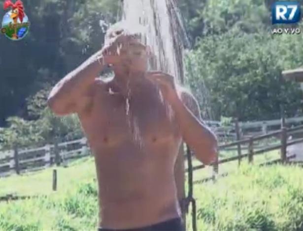 O modelo Gustavo Salyer toma banho na área externa da fazenda (30/5/12)