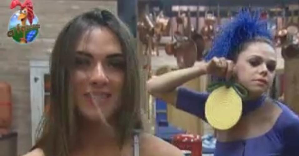 Léo Aquilla (esq) mostra brinco feito com material da cozinha para Nicole Bahls (31/5/12)