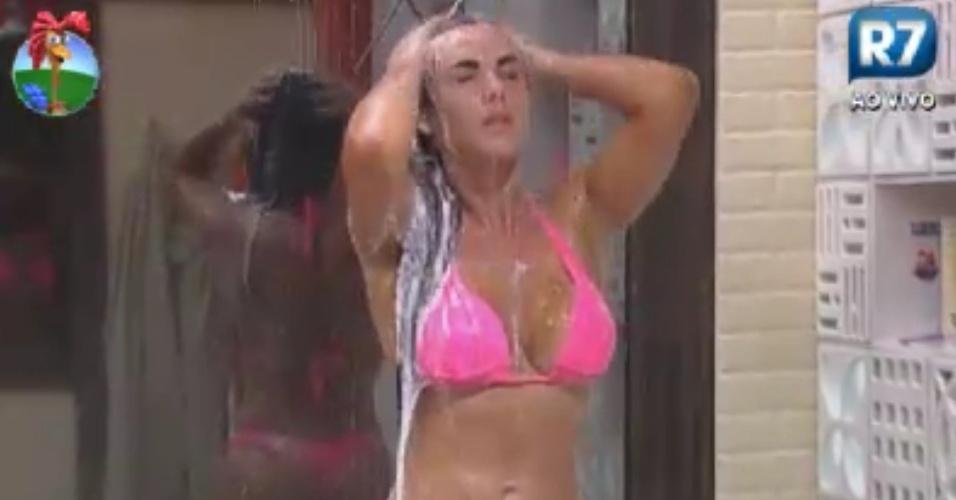 Nicole Bahls usa biquíni rosa fluorescente para tomar banho em