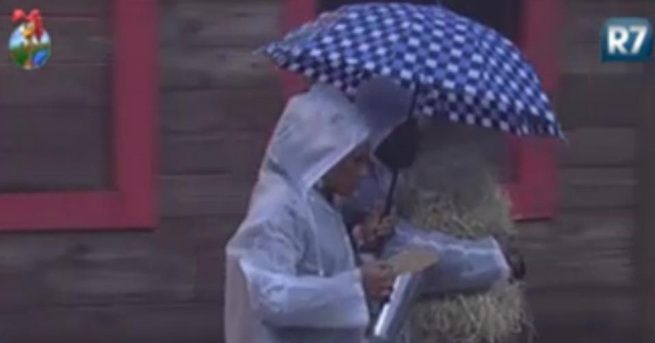 Lui Mendes e Simone Sampaio usam capas e guarda-chuvas para se proteger do mau tempo (5/6/12)