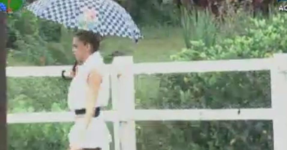 Léo Áquilla vai com guarda-chuva para a área dos animais (7/6/12)