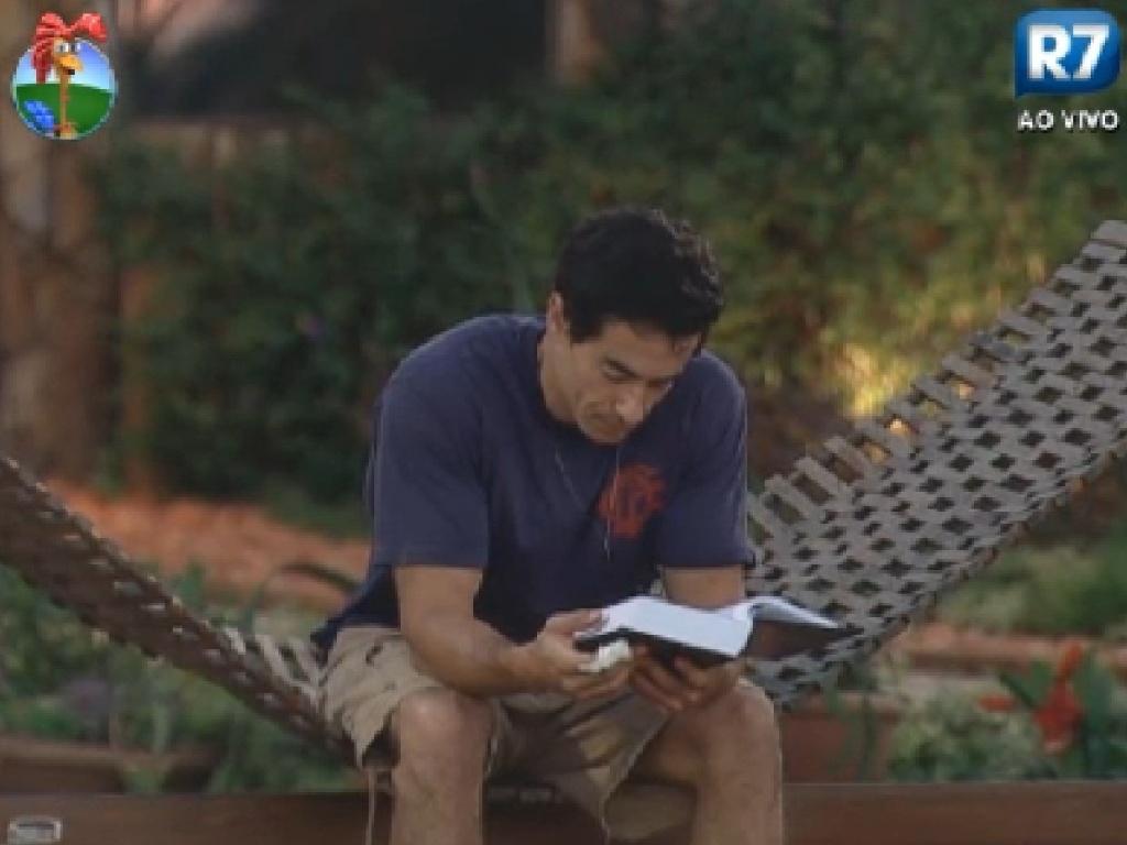 Felipe Folgosi lê sozinho na área externa da sede (14/6/12)