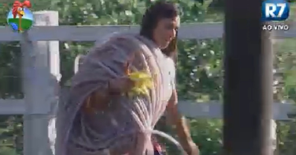 Nicole Bahls carrega mangueira para cuidar da horta (15/6/12)