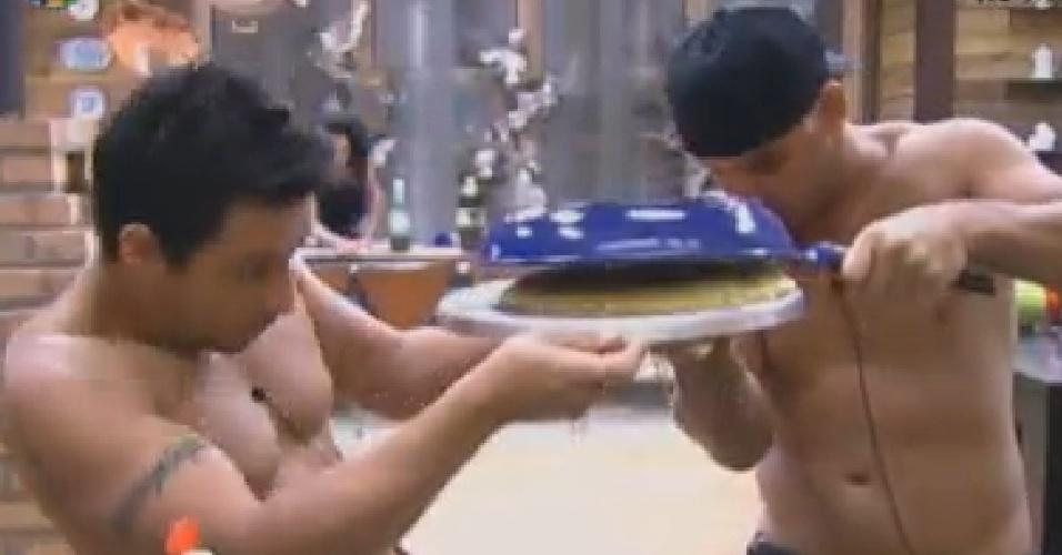 Vavá (esq.) e Rodrigo Capella (dir.) preparam omelete com ovo de avestruz para os peões (30/6/12)