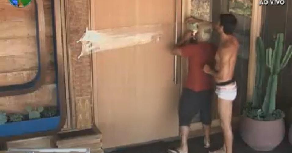 Rodrigo Capella e Diego Pombo colocam plástico na porta para pregar peça em peoas (5/7/12)