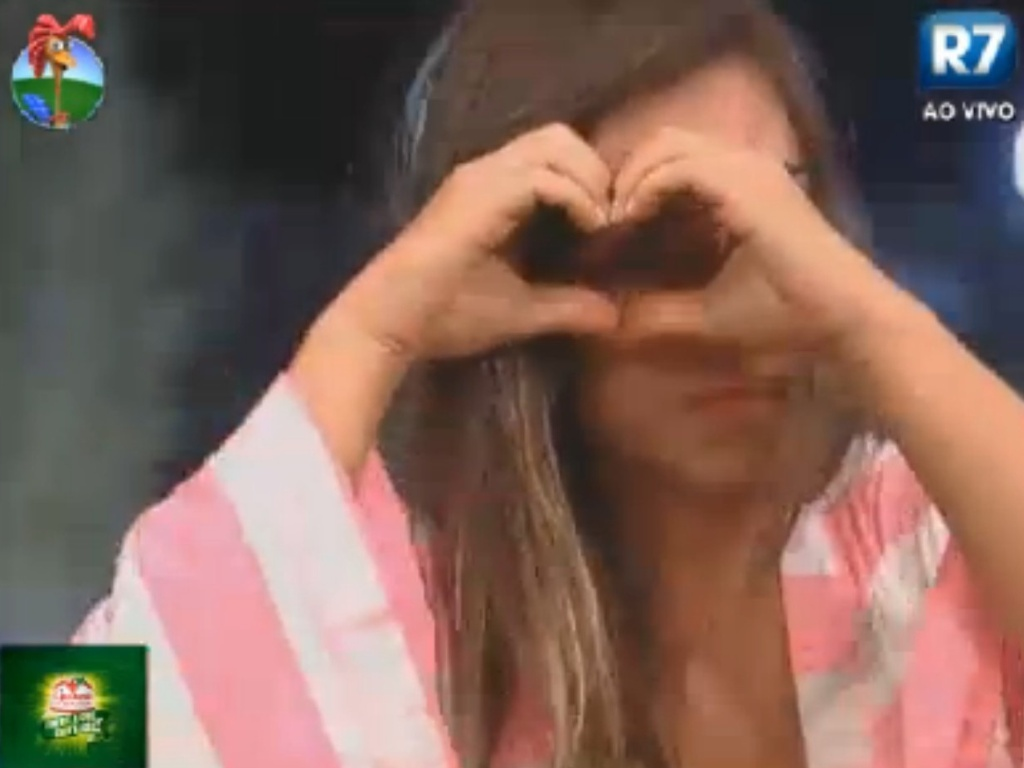 Nicole Bahls se despede das cabras fazendo coração com as mãos (17/8/12)