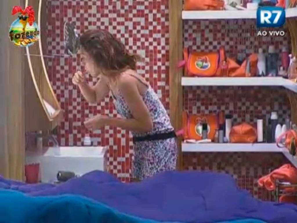 Claudia escova os dentes com a torneira aberta