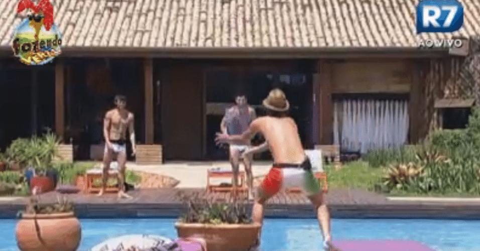 Halan, Thyago e Haysam brincam com almofada. O objetivo é agarrar a peça arremessada pelo colega do outro lado da piscina