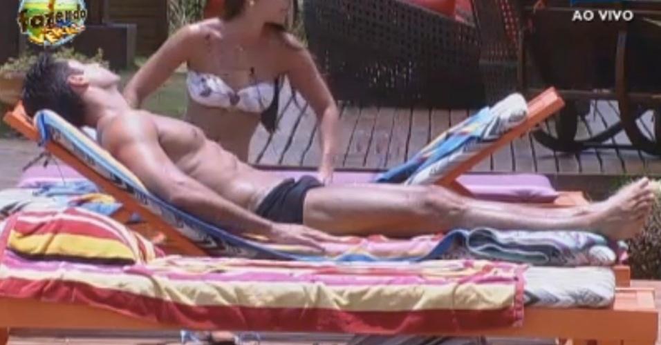 Flavia e Dan conversam perto da piscina