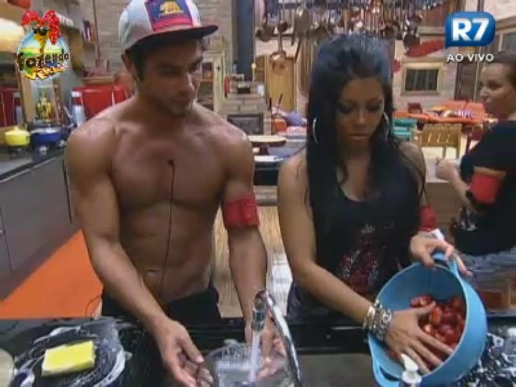 Victor lava louça e Natália lava os morangos da sobremesa