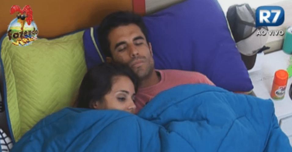 Dan deita na cama com Flávia para esperar o duelo contra Thyago
