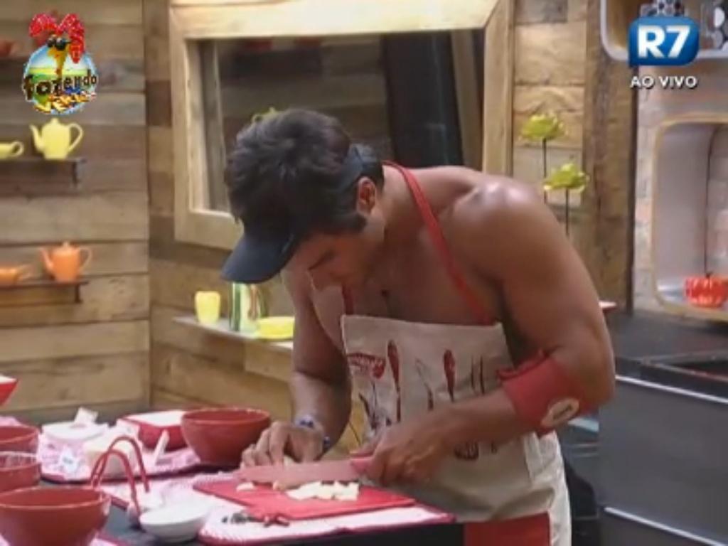 Victor pica alho para prepara o almoço