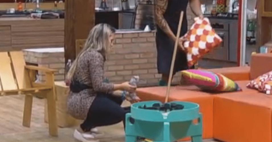 Ísis carrega o balde e o produto para limpar o banheiro