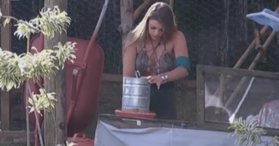 Manoella limpa a ferramenta para dar comida às galinhas