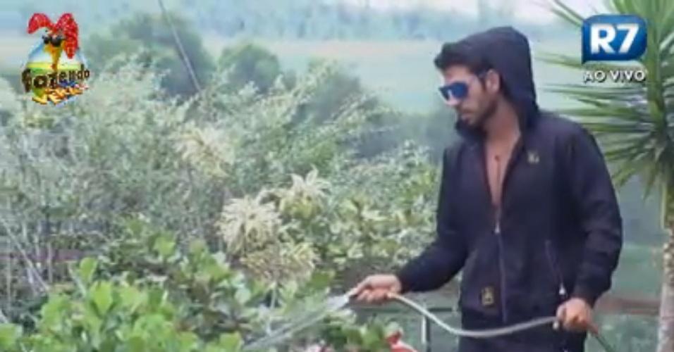 Thyago passa a manhã regando as plantas com a mangueira