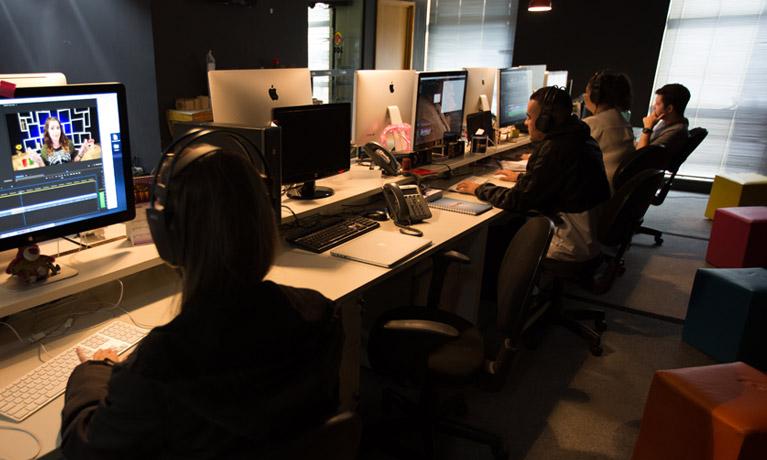 escritório do UOL com algumas pessoas trabalhando em seus computadores